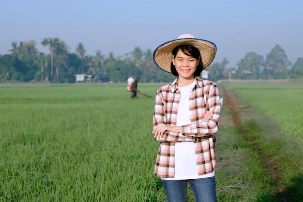 Uma agricultora vestindo uma camisa listrada posa com os braços cruzados e um rosto sorridente em um campo.