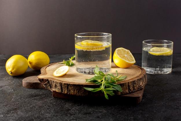Uma água de vista frontal com bebida fresca de limão com limões fatiados, juntamente com limões inteiros e folhas dentro de vidros transparentes no escuro
