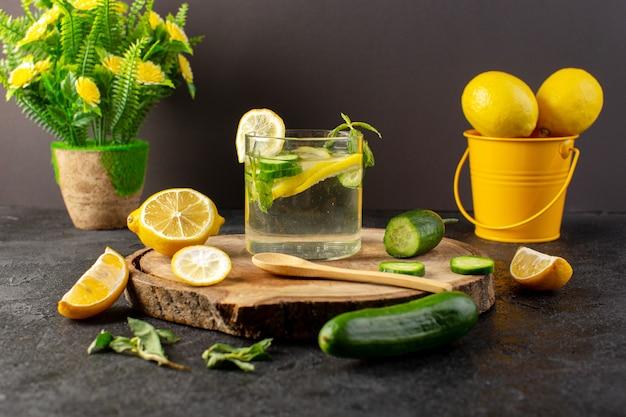 Uma água de vista frontal com bebida fresca de limão dentro de vidro com folhas verdes com cubos de gelo com pepino em limões fatiados no escuro