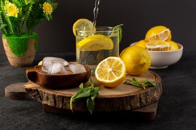 Uma água de vista frontal com bebida fresca de limão dentro de vidro derramando com folhas verdes com cubos de gelo com limões fatiados no escuro