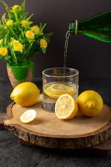Uma água de vista frontal com bebida fresca fresca de limão derramando no copo com limões fatiados, juntamente com limões inteiros e flores no escuro