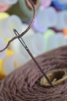Uma agulha de costura com linha marrom passando pelo buraco da agulha. macro.