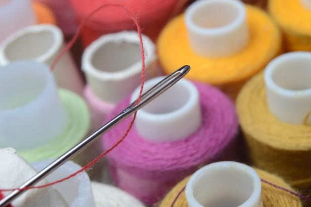 Uma agulha de costura com linha vermelha passando pelo buraco da agulha