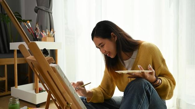 Uma alegre jovem pintora está sentada no chão em frente a uma tela e desenhando em seu estúdio.