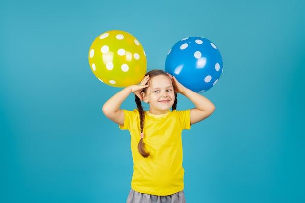 Uma alegre menina com tranças em uma camiseta amarela segura balões em sua cabeça como orelhas
