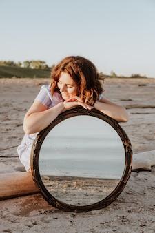 Uma alegre mulher morena de vestido azul sorri, caminha pela praia e aproveita o sol brilhante