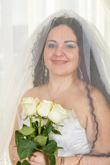 Uma alegre noiva judia com o rosto coberto por um véu com um buquê de rosas brancas antes de realizar o rito huppa. foto vertical
