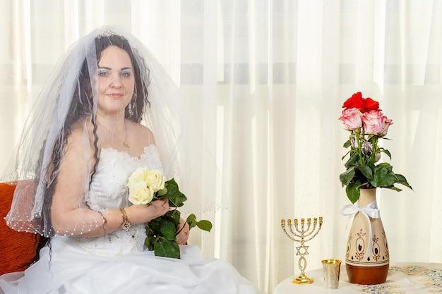 Uma alegre noiva judia com o rosto coberto por um véu com um buquê de rosas brancas se senta em uma sinagoga antes de realizar a cerimônia huppa em uma mesa com flores