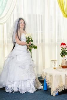 Uma alegre noiva judia com o rosto coberto por um véu e um buquê de rosas brancas está na sinagoga antes de realizar o rito huppa em uma mesa com flores. foto vertical