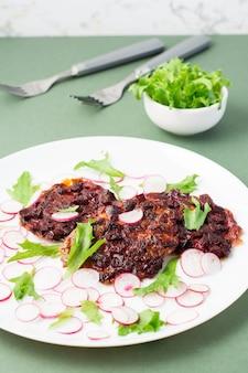 Uma alternativa à proteína da carne é o bife de beterraba com vegetais e ervas em um prato. dieta flexitariana. visão vertical