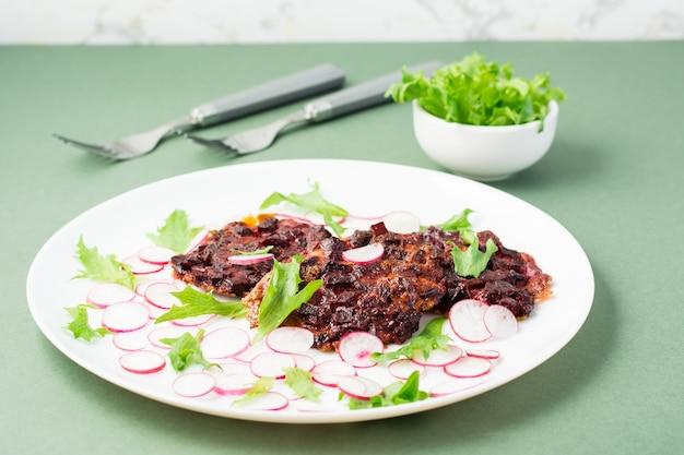 Uma alternativa à proteína da carne é o bife de beterraba com vegetais e ervas em um prato. dieta flexitariana