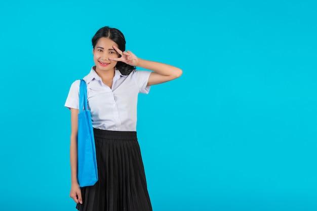 Uma aluna asiática que gira um saco de pano e mostra vários gestos em um azul.