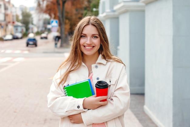 Uma aluna caminha pela cidade com uma xícara de café e um caderno. rapariga estudante com cabelos brancos