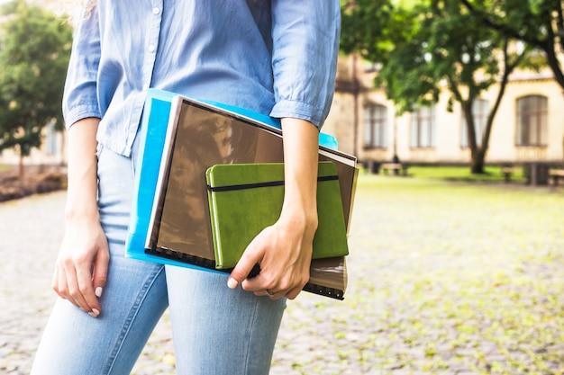 Uma aluna com cabelo longo encaracolado está segurando materiais de estudo em pastas