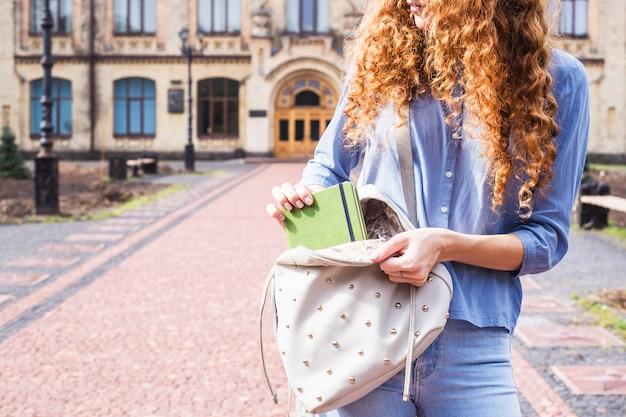 Uma aluna com cabelo longo encaracolado leva um caderno de sua mochila