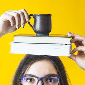Uma aluna de óculos está segurando uma pilha de livros e uma xícara de café