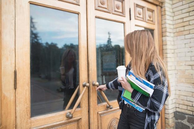 Uma aluna de roupas casuais, livros e cadernos nas mãos abre a porta da universidade