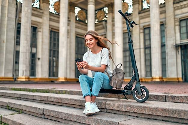 Uma aluna encantadora senta-se nos degraus de uma scooter perto do campus e usa seu smartphone.