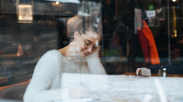 Uma aluna linda de óculos e um suéter branco sentada em um café depois da escola, escrevendo em um caderno