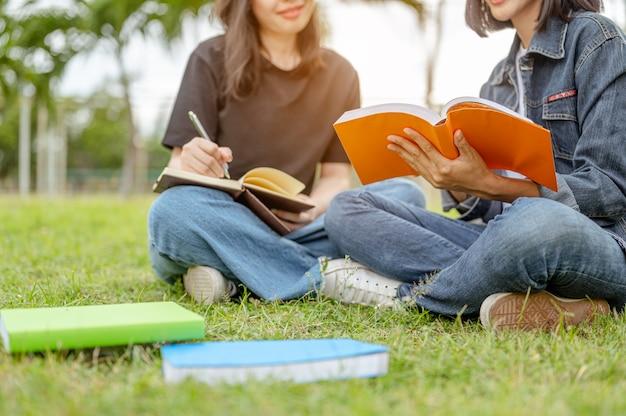 Uma aluna sentada dando aulas de reforço com amigos no parque natural universidades livros de conhecimento