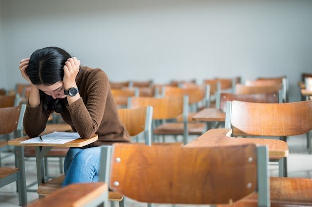 Uma aluna sentada em uma sala estressante