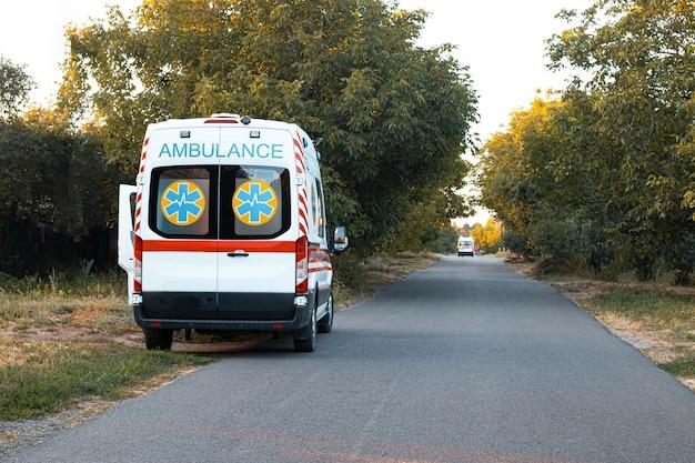 Uma ambulância está estacionada na beira da estrada.