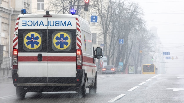 Uma ambulância levou o paciente para a clínica com os indicadores luminosos ligados. mau tempo lá fora, chuva com neve molhada.