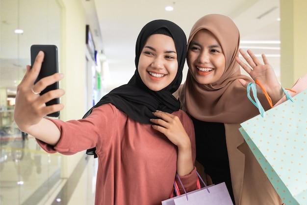 Uma amiga asiática hijab tira um autorretrato usando o telefone celular e segura uma sacola de compras