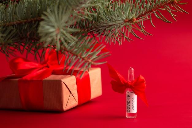 Uma ampola da vacina covid fica embaixo de um galho de árvore de natal