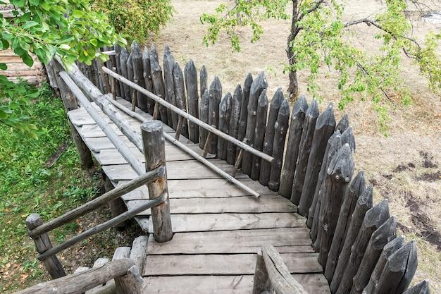 Uma antiga paliçada de madeira feita de troncos pontiagudos em uma antiga vila russa. estilo de vida rural vintage