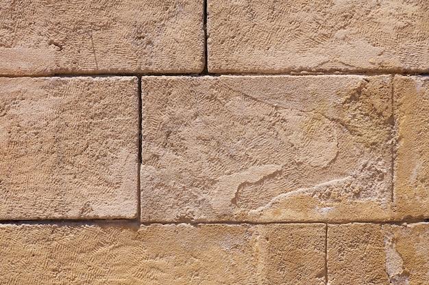 Uma antiga parede rara de blocos de pedra como pano de fundo.