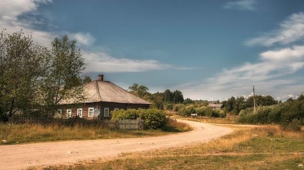 Uma antiga vila com casas de madeira e uma estrada de terra no norte da rússia no verão
