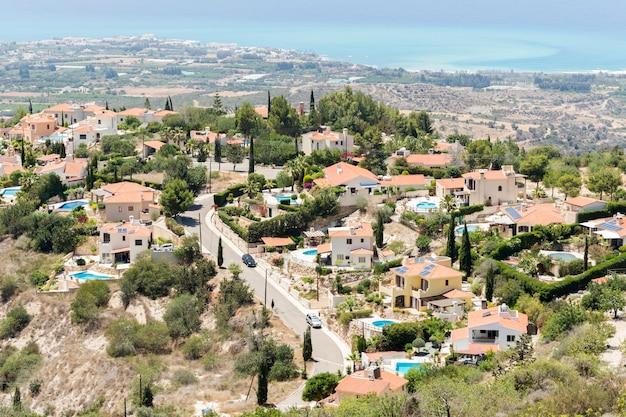 Uma área residencial com piscinas, casas localizadas na encosta de uma colina com vista para o mar
