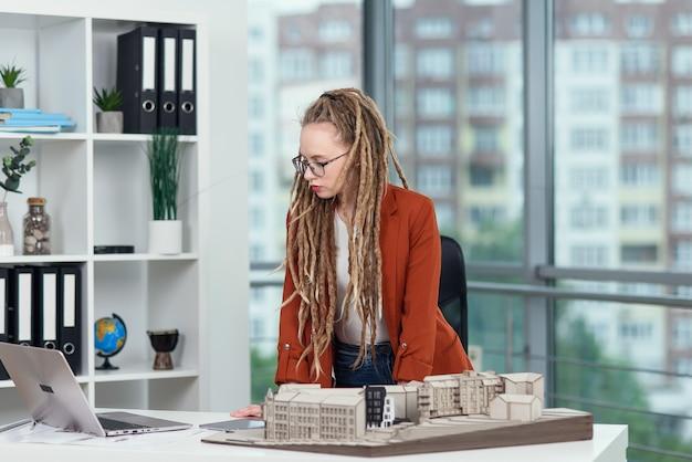 Uma arquiteta bonita com dreadlocks trabalha com maquete de papelão da casa no escritório de arquitetura