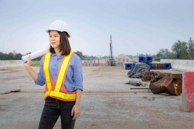 Uma arquiteta líder de pé na construção da ponte, usando um capacete de segurança e segurando a planta do projeto.
