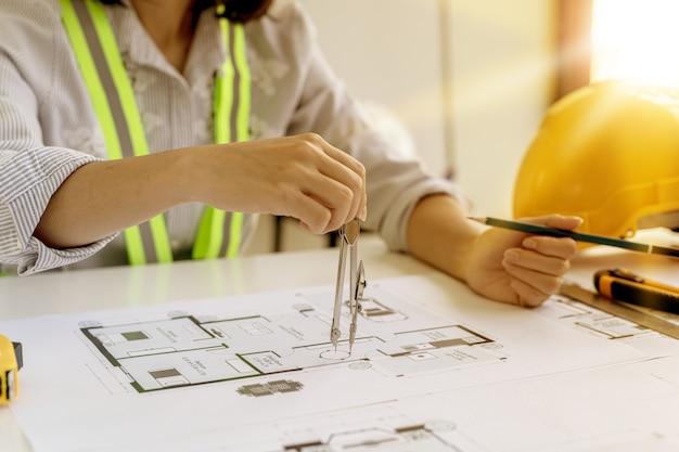 Uma arquiteta usa uma rotatória para desenhar os projetos da casa, ela verifica as plantas da casa que ela fez antes de enviá-las aos clientes, ela projeta a casa e o interior.