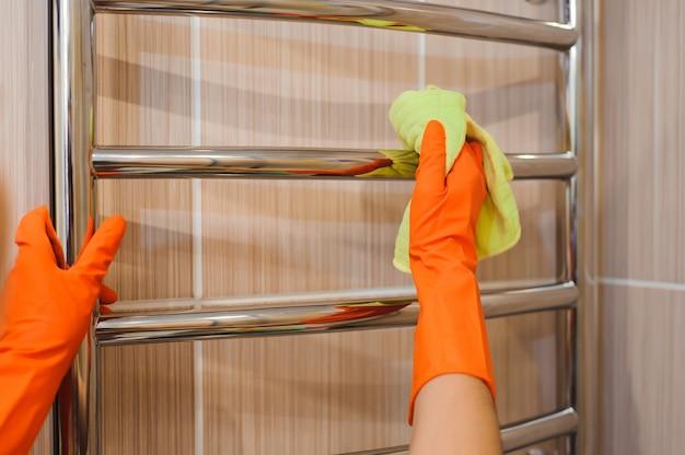 Uma arruela de mulher está limpando a superfície de azulejos no banheiro