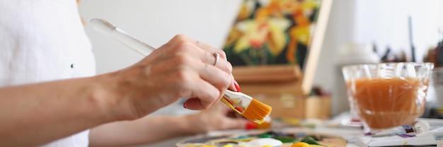 Uma artista feminina se senta a uma mesa e mistura tinta em uma paleta com um pincel para passatempo para um jovem