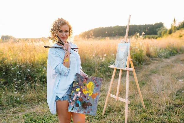 Uma artista talentosa ao ar livre está misturando tintas para seu novo projeto enquanto segura pincéis.