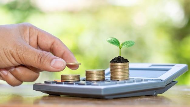 Uma árvore crescendo em uma pilha de moedas e a mão de um homem colocando moedas em uma pilha de ideias de crescimento econômico de moedas.