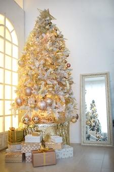Uma árvore de natal com decoração dourada se reflete no espelho