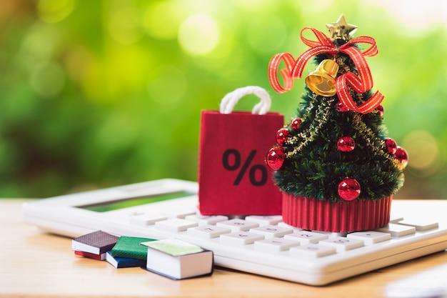 Uma árvore de natal lindamente decorada colocada em uma calculadora branca