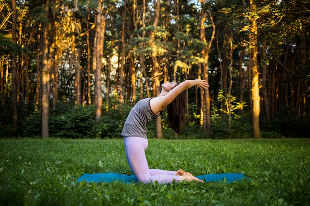 Uma atleta feminina faz uma pose de ioga ushtrasana ao pôr do sol na floresta