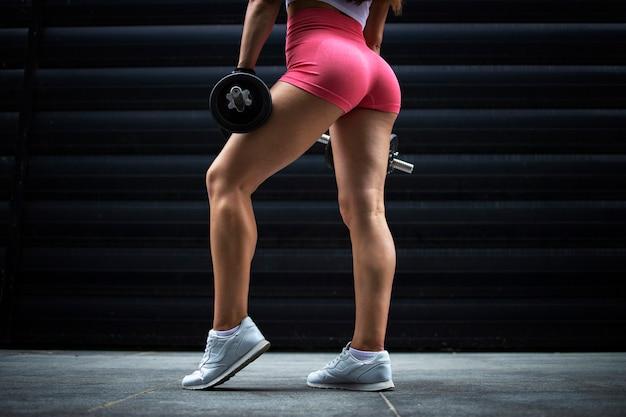 Uma atleta irreconhecível e musculosa com pernas fortes, posando no ginásio contra um fundo preto
