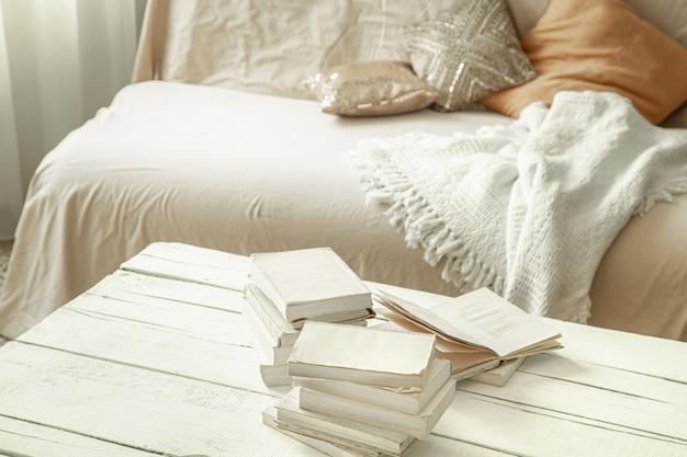 Uma atmosfera íntima e caseira com livros em uma grande mesa iluminada.