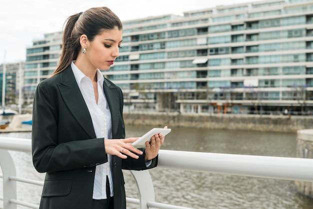 Uma atraente jovem empresária em pé perto do corrimão usando telefone celular