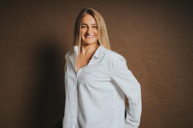 Uma atraente mulher loira, branca, com uma camisa branca, posando em um fundo marrom