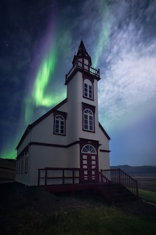 Uma aurora bonita dançando sobre uma igreja na islândia.