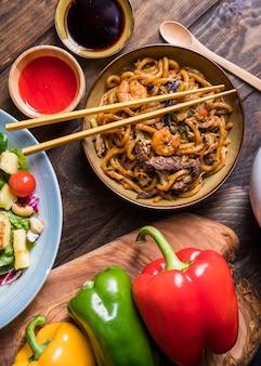Uma bacia da vista aérea de carne de vaca deliciosa tailandesa; camarão com macarrão udon e molhos
