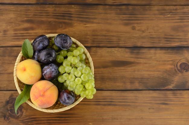 Uma bacia de verão saboroso, maduro frutifica na tabela de madeira marrom.